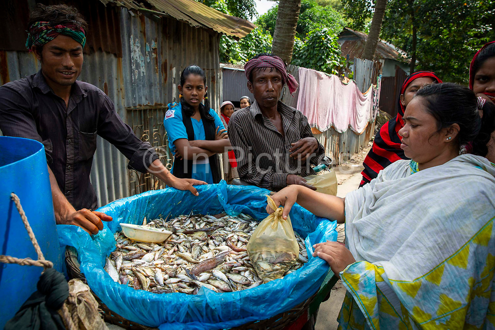 A woman buying a bag of mixed fresh fish from a mobile fish seller in the Karail district of Dhaka on the 24th of September 2018 in Dhaka, Bangladesh.