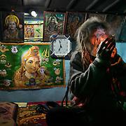 A Sadhu smoking marijuana in his home. In the Himalaya.