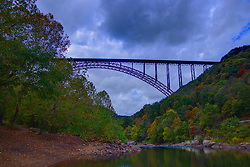 The New River Gorge Bridge - shot on a very overcast and cloudy day, the rusty patina on the bridge and the brilliance of the fall colors of the trees and foliage shine.  The bridge is one of the longest single arch steel span bridges in the world, built in 1977.<br /> <br /> HDR (High Dynamic Range) post processing applied.   Black and White, monochrome or greyscale