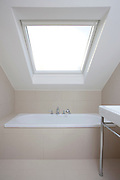 bathroom with sloping ceiling and velux window and sink in foreground