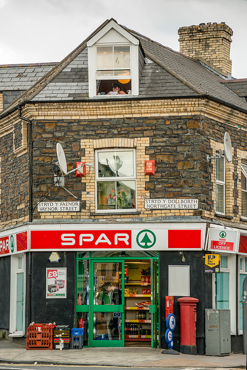 Neighborhood Corner Market in Aberystwyth Wales with man in upper window. Open Edition Prints and Editorial Usage.