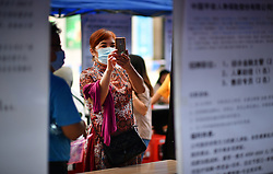 HAIKOU, April 18, 2020  A job hunter takes pictures of job information at a job fair in Haikou, south China's Hainan Province, April 18, 2020. More than 100 enterprises took part in the job fair Saturday, offering 4,000 job opportunities. (Credit Image: © Guo Cheng/Xinhua via ZUMA Wire)