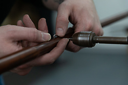 Minute holes are drilled for retaining pins that will hold the spring in place on the shaft of an umbrella. Craftspeople at Fox Umbrellas Ltd, a company in Croydon, Surrey, that has been going for over 150 years hand build quality umbrellas. Croydon, Surrey, March 06 2019.
