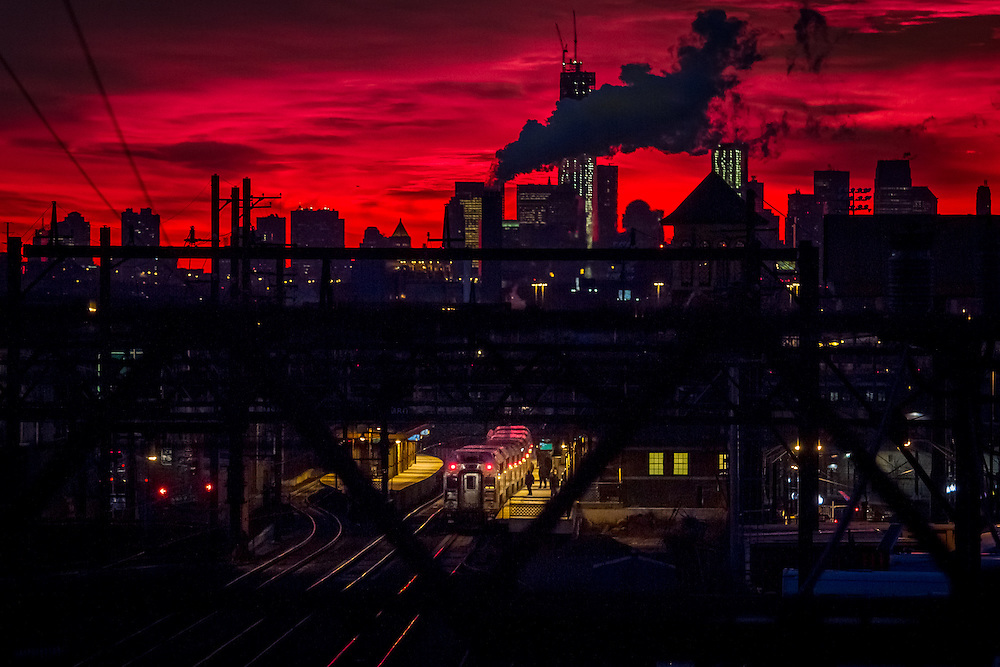 A NJ Transit train stops at Newark Broad St Station en route to New York which is awakening to a red sky.