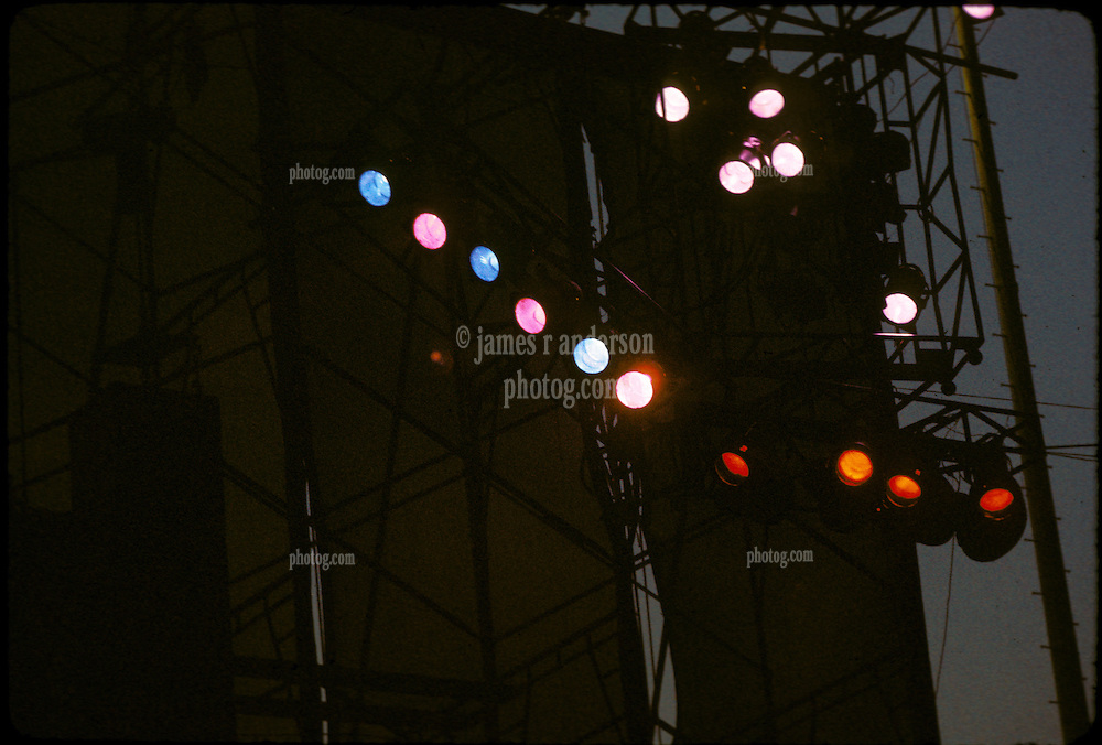 Lights at right upper Wall of Sound rigging. Grateful Dead Live at Dillon Stadium, Hartford, CT 31 July 1974. Shot at Dusk, some sunlight still in sky behind wind scrim.