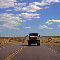 South America, Argentina, Patagonia. Pick-up truck travels the lonely highway through Patagonia.