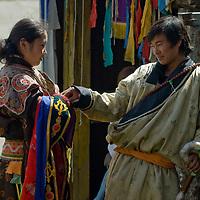 Buddhist Tsam dancers flirt as they wait to perform at the national Naadam festival in Ulaanbaatar, Mongolia.