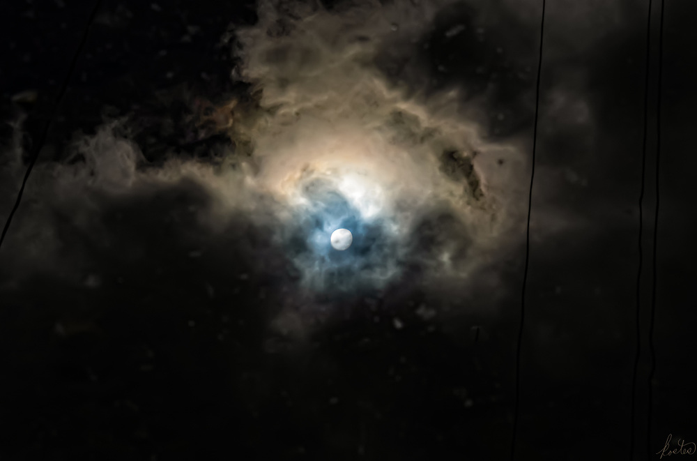 A reflection of the sky in a rain puddle, over asphalt, giving it a dark background.