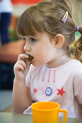 Child eating a biscuit in creche at adult education centre,
