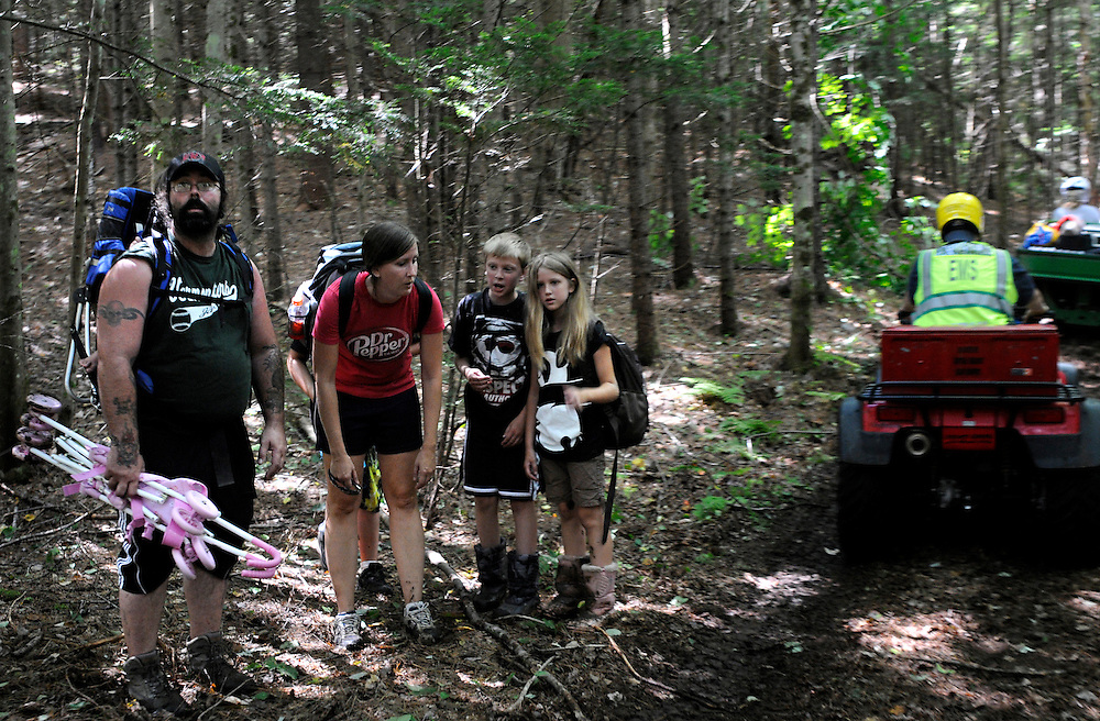 Tom Melcher, left, and his family step to the side of a trail paralelling Camp Brook Road in Bethel as a crew of Bethel firefighters and White River Valley EMT's make their way toward Rochester Tuesday, August 30, 2011. After being stranded without power, since Sunday, Melcher walked out toward Bethel Village. <br /> Valley News - James M. Patterson<br /> jpatterson@vnews.com<br /> photo@vnews.com