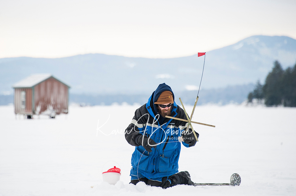Setting a tip up on Meredith Bay during the Great Meredith Rotary Ice Fishing Derby.  (Karen Bobotas Photographer)