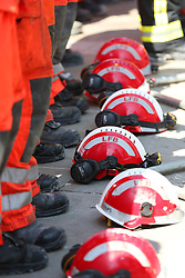 Firefighters lay their helmets on the ground as they observe a minute's silence near to Grenfell Tower in west London after a fire engulfed the 24-storey building on Wednesday morning.