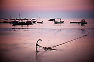 Myanmar, Ngapali. Sunrise at the Ngapali Beach.<br /> Every single morning all the fisherman from the little village at Ngapali Beach come back home with their night catch. At the beach all the women wait for them and afterwards work with drying and selling fish and other creatures from the sea begins.