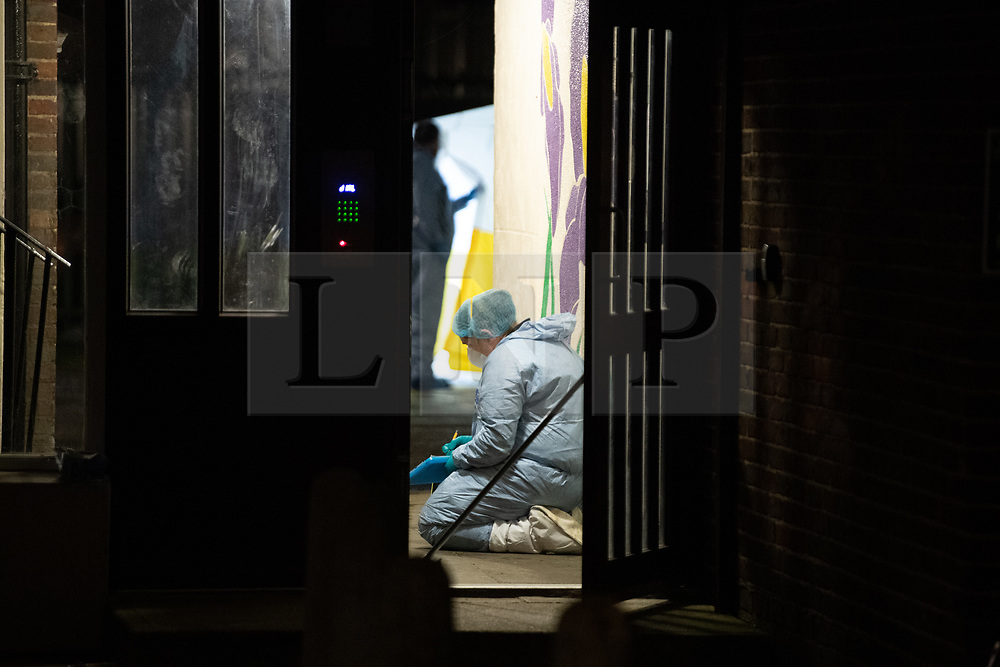 © Licensed to London News Pictures. 06/02/2021. London, UK. A forensic investigator kneels on the floor inside a doorway to a block of flats on Wisbeach Road. Metropolitan Police are investigating multiple incidents of serious violence, including a fatal stabbing, in south London. One case was reported at 20:08GMT on Wisbeach Road, Croydon, where two males had suffered stab injuries. One male was taken to hospital prior to police arrival; condition not life-threatening. Another male was found at the scene. Despite the best efforts of paramedics, he was pronounced dead at the scene. Photo credit: Peter Manning/LNP