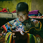 Monk checking his phone. The Tshechu of the Gasa monastery on the road leading to Laya. Tshechu are annual religious Bhutanese festivals held in each district on the tenth day of a month of the lunar Tibetan calendar. Tshechus are large social gatherings, which perform the function of social bonding among people of remote and spread-out villages.