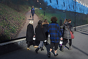 Lunch box-carrying women pass the artwork by British-Iranian photographer and film director, Mitra Tabrizian, on 2nd March 2017, in The Cut, London borough of Southwark, England.