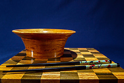 Hand turned wooden oak bowl on wooden checkerboard and dark blue background with decorated black colored chopsticks