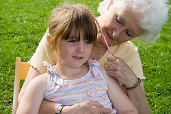 Grandmother sitting with her granddaughter; smiling,
