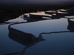"""Pamukkale, meaning """"cotton castle"""" in Turkish, is a natural site in Denizli Province in southwestern Turkey. The city contains hot springs and travertines, terraces of carbonate minerals left by the flowing water. It is located in Turkey's Inner Aegean region, in the River Menderes valley, which has a temperate climate for most of the year."""
