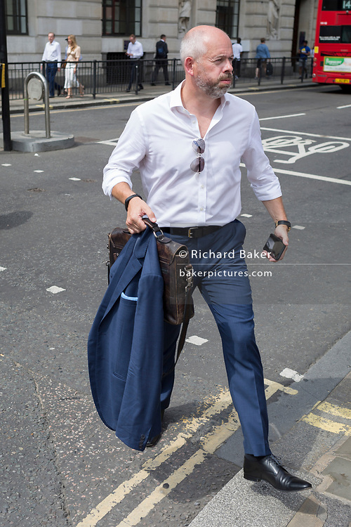 As heatwave temperatures climb to record levels - the hottest day of the year so far - a Londoner in the City of London (the capital's financial district aka the Square Mile) takes off his jacket on Threadneedle Street, on 25th July 2019, in London, England.