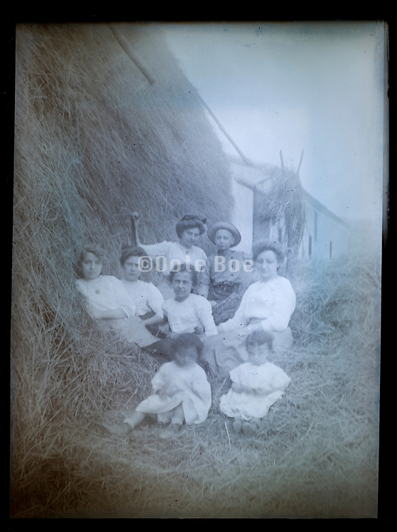 fading glass plate photo of a family sitting in a haystack France ca 1920s