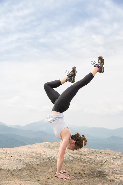 Woman on the summit of Cascade mountain doing a handstand