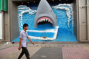 A man walks past a depiction of a shark at a small amusement park in the new district of Yangzhou, Jiangsu Province, China on 19 July 2012. While the Chinese government has tried various ways to cool down the property market, real estate prices have still seen a steady increase in recent years, proving hard for the country to move away from an investment driven economy.