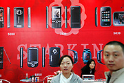 Visitors walk past a large poster showing Chinese clones of brand name mobile phones, including those of iPone models, at a technology fair in Shenzhen, Guangdong Province, China on 17 November 2009.