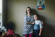 """GUNTERSVILLE, AL – SEPTEMBER 3, 2019: Brianna Barker, 34, stands with her 8 year-old son, Callen, in his bedroom. As the founder of Huntsville's chapter of the International Cesarean Awareness Network (ICAN), Barker facilitates support meetings and moderates online forums on topics surrounding cesarean birth in an effort to support mothers seeking a vaginal birth after cesarean (VBAC). <br /> <br /> Barker's first child was born prematurely by cesarean. Reflecting on the birth of Callen, her second child, Barker recalls feeling alone in her effort to have a normal vaginal birth. """"It was really hard. I didn't have a doula or any support network. Even today I have recurring nightmares where I'm alone in a dark hospital in labor. In my subconscious, I was just so alone."""" With their third and fourth children the Barkers chose an out of hospital birth experience – driving 2 ½ hours to Tennessee for every prenatal appointment. During this time, Barker was involved in the fight to legalize midwifery in Alabama. """"I knew I had many privileges that many others didn't have. So I went to Montgomery. And the other mom's and I – we all have this collective PTSD from dragging our screaming babies around Montgomery, marching to hearings and all that, just so there would be accountability. It's incredible the amount of barriers to access for v-backs, but I was able to have a vaginal birth with Callen, and for that I'm so grateful."""" <br /> <br /> Although midwifery has been legalized in Alabama, from Barker's perspective """"the fight is not really over."""" Today, many hospitals still ban vaginal births after cesarean. """"There's just so much misinformation, even about what the guidelines are,"""" Barker says. """"They're essentially mandating surgery for a large percentage of their patients, and I don't want that for other people. I want to make a difference, so other mom's can have the same experience I had. And if enough moms and families come together with more info"""