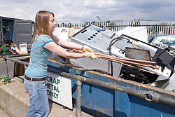 Woman recycling scrap metal into a skip at the city tip,