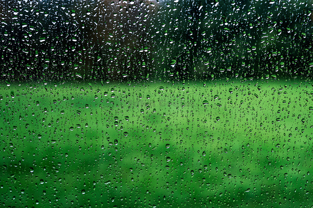 Rain streaked window looking out.