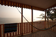 Belize, Central America - Morning light and beach from the beach house deck at tradewinds cottages in Placencia.