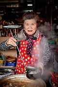 Portrait of a woman preparing a soup at Jagalchi Fish Market in Busan, South Korea.