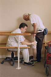 Prosthetist with elderly patient in mobility centre; fitting belowknee (transtibial) prosthesis,