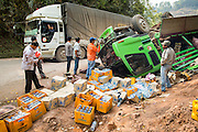 15 MARCH 2013 - ALONG HIGHWAY 13, LAOS:  A truck hauling materials to China through Laos passes an overturned Beer Lao truck on Highway 13 north of Luang Prabang. The paving of Highway 13 from Vientiane to near the Chinese border has changed the way of life in rural Laos. Villagers near Luang Prabang used to have to take unreliable boats that took three hours round trip to get from the homes to the tourist center of Luang Prabang, now they take a 40 minute round trip bus ride. North of Luang Prabang, paving the highway has been an opportunity for China to use Laos as a transshipping point. Chinese merchandise now goes through Laos to Thailand where it's put on Thai trains and taken to the deep water port east of Bangkok. The Chinese have also expanded their economic empire into Laos. Chinese hotels and businesses are common in northern Laos and in some cities, like Oudomxay, are now up to 40% percent. As the roads are paved, more people move away from their traditional homes in the mountains of Laos and crowd the side of the road living off tourists' and truck drivers.   PHOTO BY JACK KURTZ