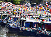 © Licensed to London News Pictures. 06/05/2013. London, UK People relax with their boats in the early morning sunshine. A Colourful gathering of canal boats in the hot bank holiday sunshine today in West London 6th May 2013. Organised by volunteers from Inland Waterways Association (IWA), The Canalway Cavalcade, which has taken place in Little Venice every year since 1983, sees around 130 boats moored along a stretch of the Grand Union Canal in London. Photo credit : Stephen Simpson/LNP