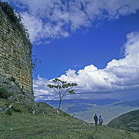 Travelers in Peru's Cordillera Central walk below the imposing fortress walls at Kuelap, a stronghold of the pre-Incan Chachapoyan culture.