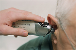 Nurse on medical ward taking patient's temperature using tympanic thermometer,