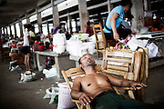 "A Chinese vendor takes a rest in a village market near YangShuo, Guilin, China, August 02, 2014. <br /> <br /> This image is part of the series ""24/7"", an ironic view on restless and fast-growing Chinese economy described through street vendors and workers sleeping during their commercial daily activity. <br /> <br /> © Giorgio Perottino"