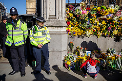 © Licensed to London News Pictures. 25/03/2017. London, UK. Police officers watch a child putting flowers down to pay his respects to the victims of Westminster terror attack outside the Houses of Parliament in London on 25 March 2017. Photo credit: Tolga Akmen/LNP
