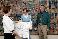 Gilford Middle School Principal Marcia Ross and 7th grade math teacher Barbara Strohm accept a check from Hannaford Store Manager Larry Poliquin in the amount of $1,000 for raising the most money during Hannaford Helps Schools program.  (Karen Bobotas/for the Laconia Daily Sun)