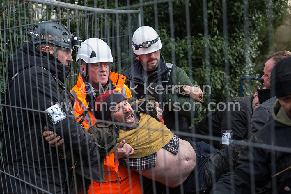 Harefield, UK. 16th January, 2020. Enforcement agents working on behalf of HS2 prevent Stop HS2 activist Mark Keir from reentering the Harvil Road wildlife protection camp in the Colne Valley after it was agreed that he could bring out dogs to a woman waiting outside belonging to a fellow activist evicted earlier in the morning from the camp after two days spent in a tree in woodland.