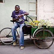A vendor in Old Havana (Cuba) selling flowers on the street out of the back of his bicycle cart.