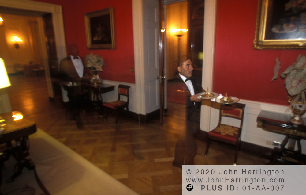 BUTLERS RUSH WITH DISHES FOR THE STATE DINNER.