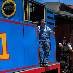Strasburg, PA – June 18, 2016: The train engineer at the train station with Thomas the Tank Engine.