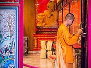 10 JANUARY 2014 - BANGKOK, THAILAND: A Buddhist novice rings a prayer gong at Wat Mangkon Kamalawat in the Chinatown section of Bangkok. It is the largest Mahayana (Chinese style) Buddhist temple in Chinatown.      PHOTO BY JACK KURTZ