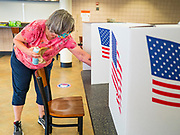 02 JUNE 2020 - WEST DES MOINES, IOWA: TORI CRISWELL, a Polk County elections worker, sanitizes voting booths on primary election day at Valley High School in West Des Moines. Because of the Coronavirus pandemic, all of the polling places in West Des Moines were consolidated to Valley High School, where voting booths were set up with social distancing in mind and booths were sanitized before they were reused. Although Iowa uses a caucus system to select presidential candidates, they use a primary election to select candidates for other offices. Statewide, the most watched race Tuesday is the Democratic Senate primary to select a candidate to run against Republican incumbent Joni Ernst.      PHOTO BY JACK KURTZ