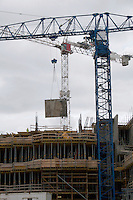 Construction cranes lifting a panel of wood in Dublin's docklands, Ireland
