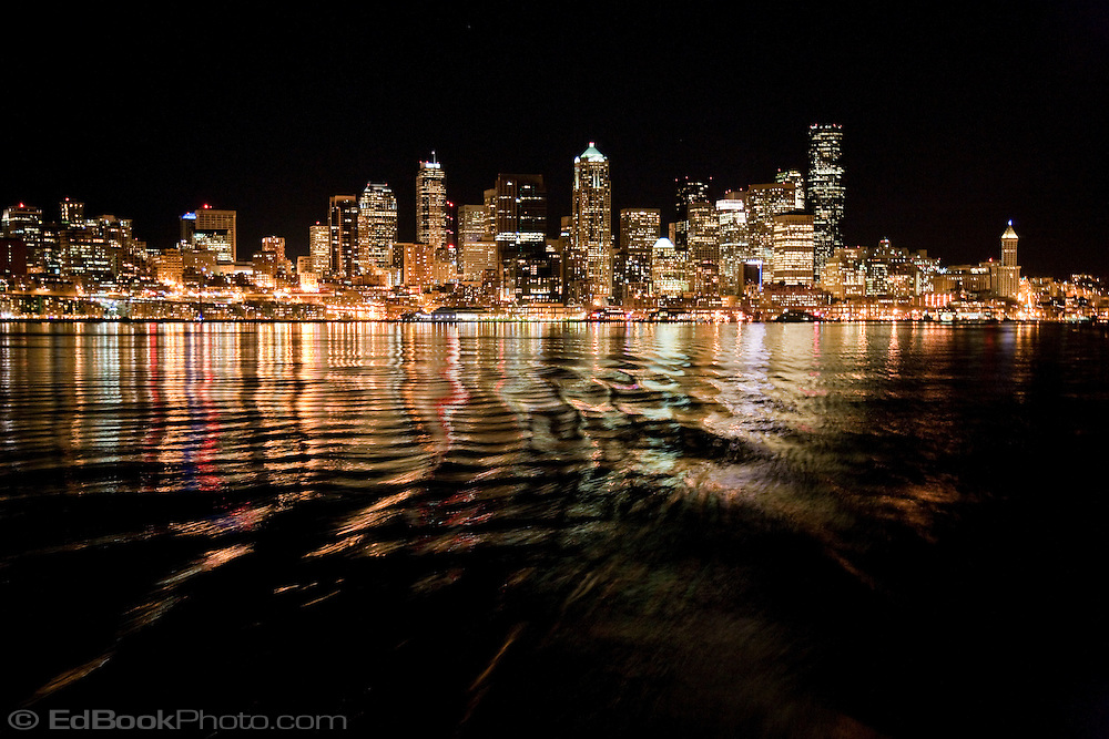 Seattle Lights at night reflecting on Puget Sound, WA, USA with ripples added from the Washington State Ferry