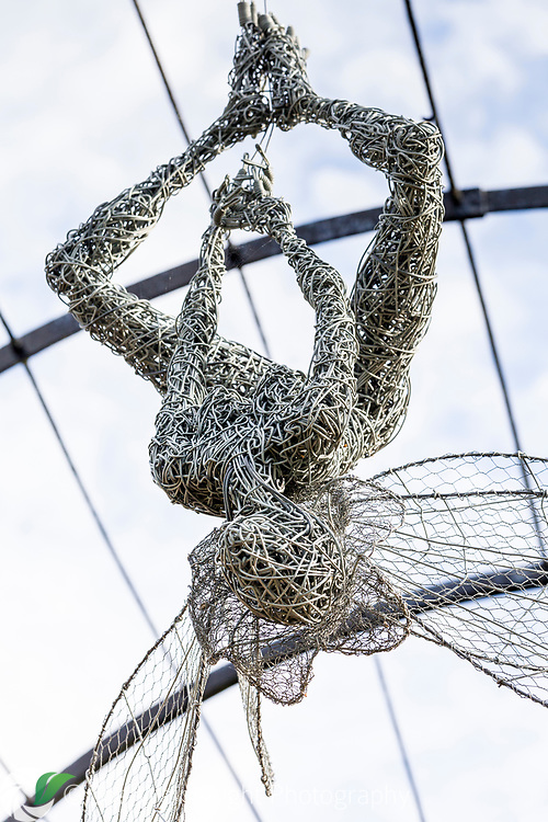 A fairy created with galvanised and stainless steel wire by artist Robin Wight, hangs in the Trellis Walk at Trentham Gardens, Staffordshire